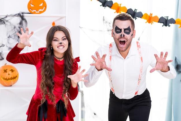 Hombre aterrador y niña en disfraces de halloween Foto gratis