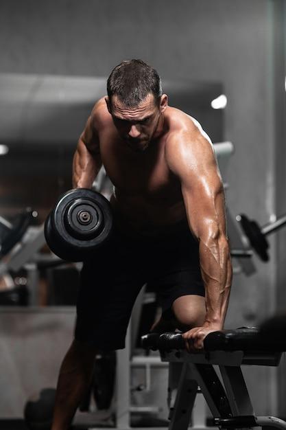 Hombre atlético entrena con pesas, bombeando sus bíceps Foto Premium