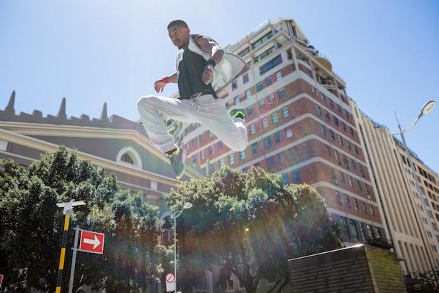 Hombre atlético haciendo parkour en la ciudad. Foto Premium