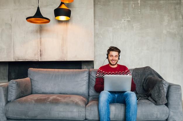 Hombre atractivo joven en el sofá en casa en invierno en auriculares, escuchando música, vistiendo suéter de punto rojo, trabajando en la computadora portátil, autónomo, sonriente, feliz, positivo Foto gratis