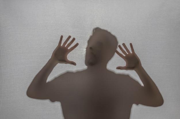 Hombre atrapado gritando detrás de tela Foto gratis