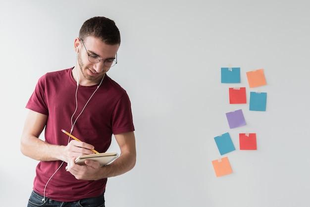 Hombre con auriculares y gafas escribiendo Foto gratis