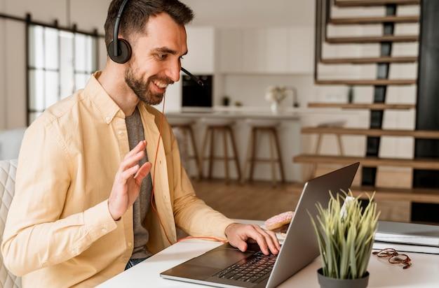 Hombre con auriculares con videollamada en portátil Foto Premium