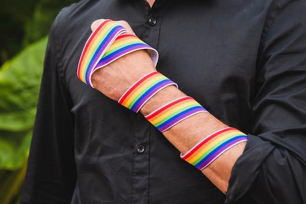 Hombre con banda en colores lgbt en mano. Foto gratis