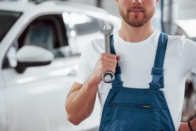 Hombre con barba clara. empleado en el uniforme de color azul trabaja en el salón del automóvil Foto Premium