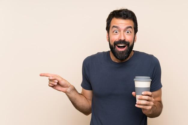 Hombre con barba sosteniendo un café sorprendido y apuntando con el dedo a un lado Foto Premium