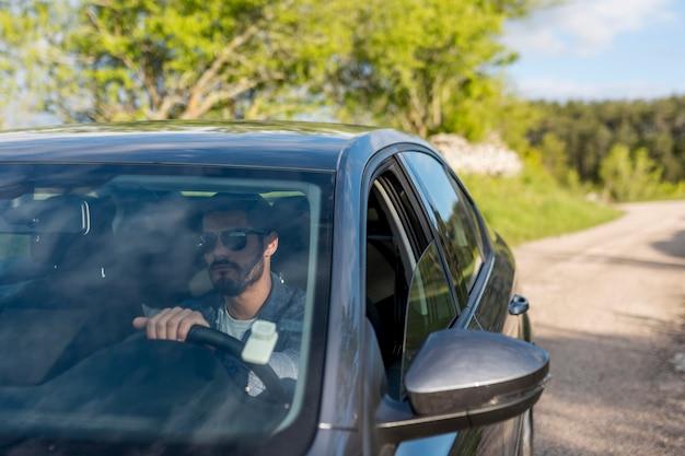 Hombre barbudo adulto conduciendo un coche en un día soleado Foto gratis
