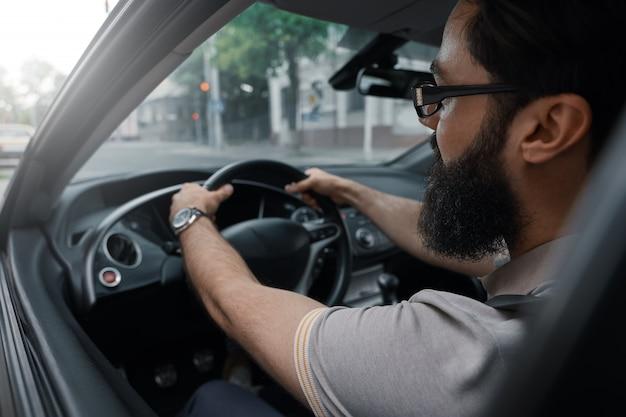 Hombre barbudo casual moderno conduciendo un automóvil Foto gratis