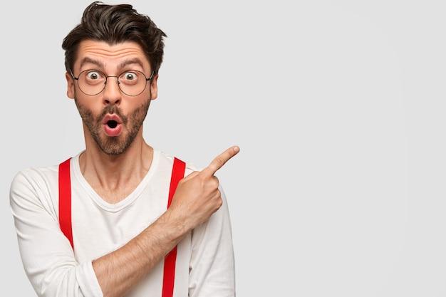 Hombre barbudo emocional tiene expresión facial sorprendida, mirada asombrada, vestido con camisa blanca con tirantes rojos, puntos con el dedo índice en la esquina superior derecha Foto gratis