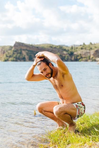 Hombre barbudo joven feliz mojando el cabello en el lago Foto gratis