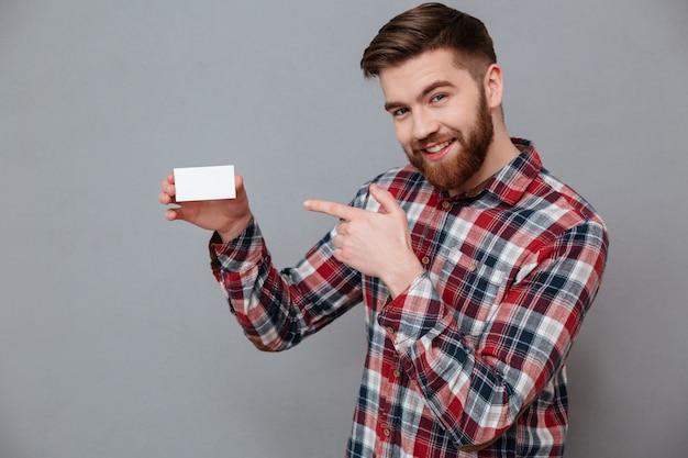 Hombre barbudo joven sonriente que sostiene la tarjeta de visita en blanco Foto gratis
