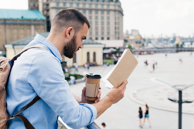 Hombre barbudo de pie cerca de la baranda con taza de café desechable mientras lee el libro Foto gratis