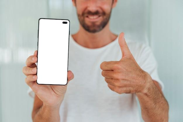 Hombre barbudo que muestra el teléfono con el pulgar hacia arriba Foto gratis