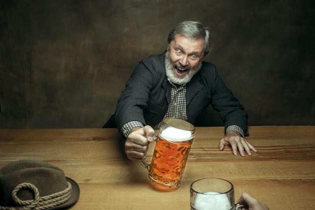 Hombre barbudo sonriente bebiendo cerveza en pub Foto gratis