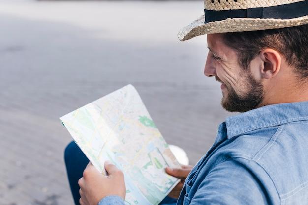 Hombre barbudo sonriente que lleva el sombrero que lee el mapa al aire libre Foto gratis