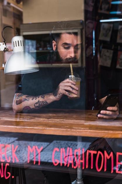 Hombre bebiendo bebida de chocolate mientras usa el teléfono móvil en café Foto gratis