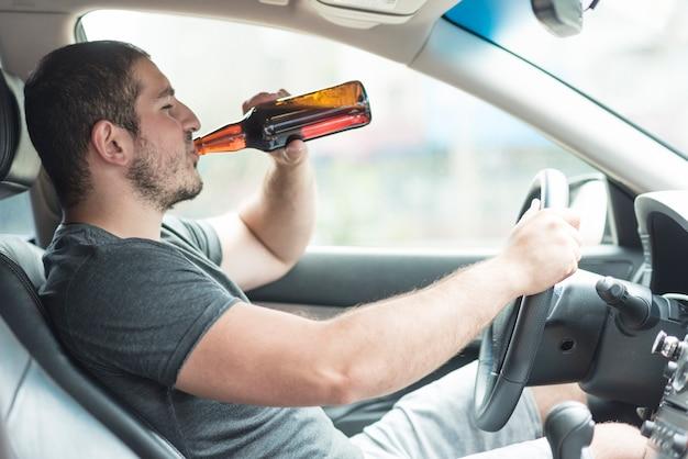 Hombre bebiendo cerveza en coche Foto gratis