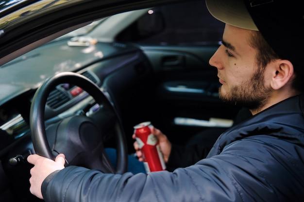 Hombre bebiendo cerveza mientras conducía un coche Foto Premium