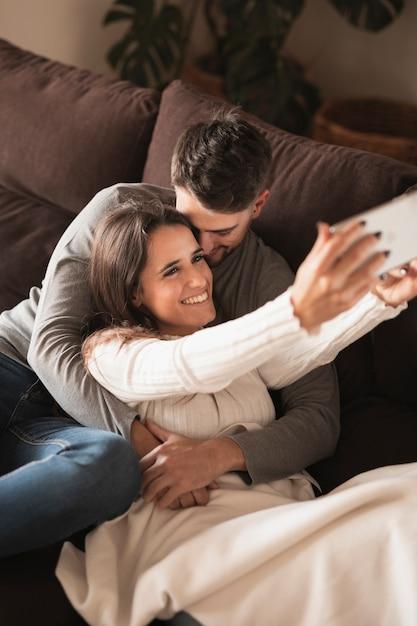 Hombre besando a mujer mientras toma selfie Foto gratis