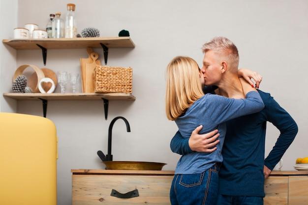 Hombre besando a su novia en la mejilla Foto gratis