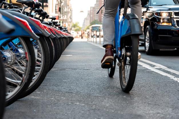 Hombre en bicicleta en la ciudad desde atrás Foto gratis