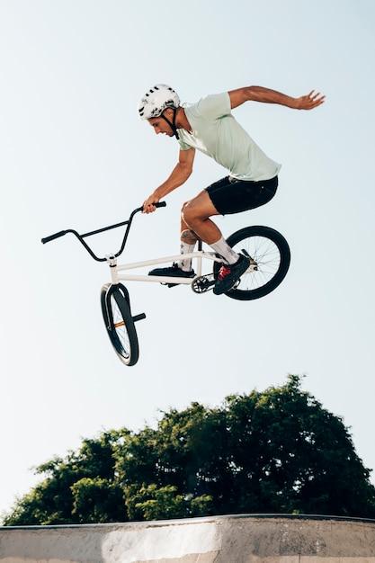 Hombre en bicicleta realizando trucos en skatepark Foto gratis