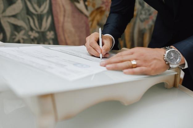 Hombre con un bolígrafo firma un documento Foto gratis