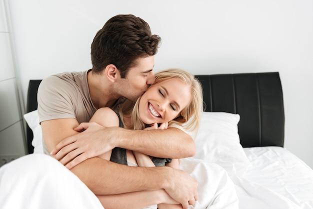 Hombre bonito joven besando y abrazando a su esposa feliz Foto gratis