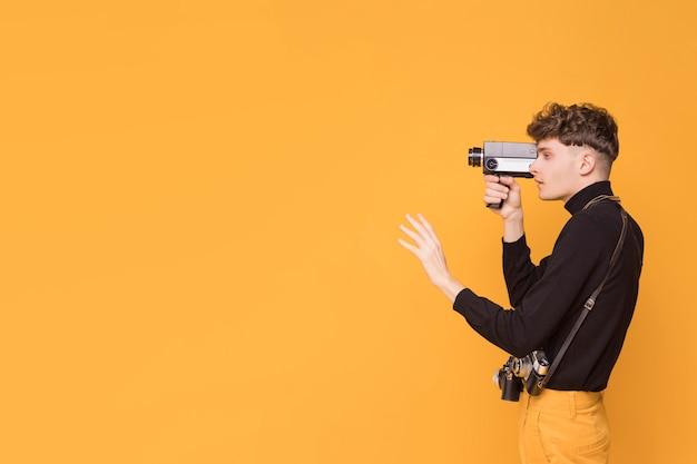 Hombre con un camcorder en un escenario amarillo Foto gratis