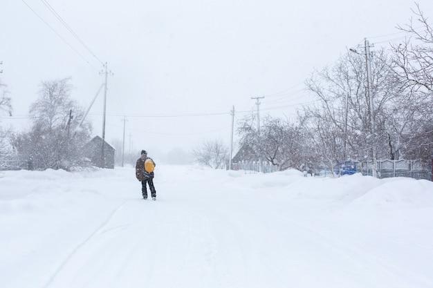 El hombre camina por la calle en invierno Foto Premium
