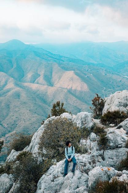 Hombre caminante solo sentado en el paisaje de montaña rocosa Foto gratis