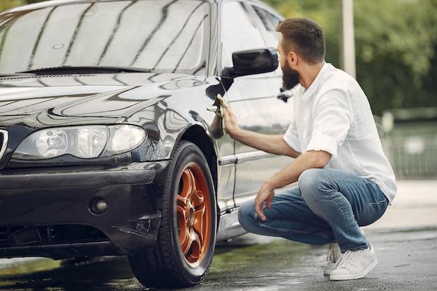 El hombre con una camisa blanca limpia un automóvil en un lavadero de autos Foto gratis