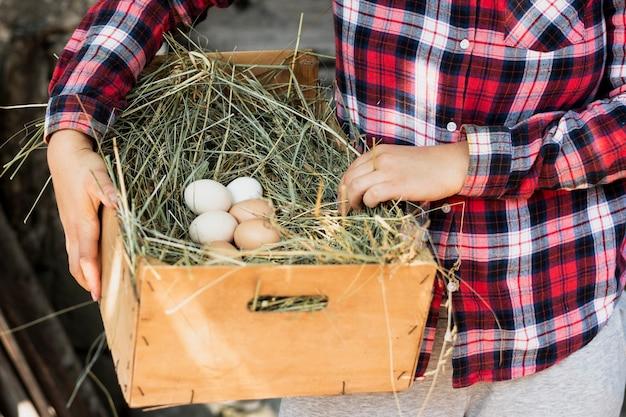 Hombre de camisa cuadrada roja sosteniendo una caja con un nido con huevos Foto gratis