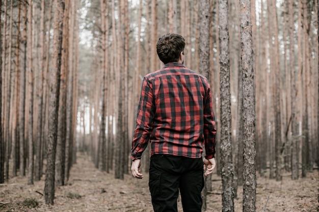Hombre En Camisa A Cuadros Roja Y Pantalon Militar Negro Perdido En El Bosque De Pinos Copia Espacio Entonado Foto Premium