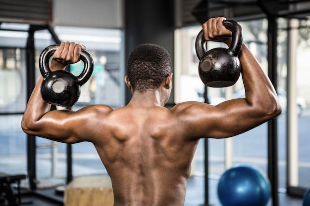 Hombre sin camisa levantando pesas pesadas en el gimnasio de crossfit Foto Premium