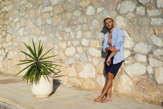Un hombre con una camisa a rayas, con un sombrero de paja, camina por las calles de un pequeño pueblo español. Foto gratis