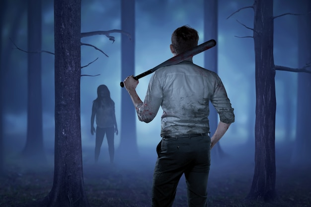 El hombre en una camisa sangrienta sosteniendo un palo sangriento quiere golpear a la dama zombie Foto Premium