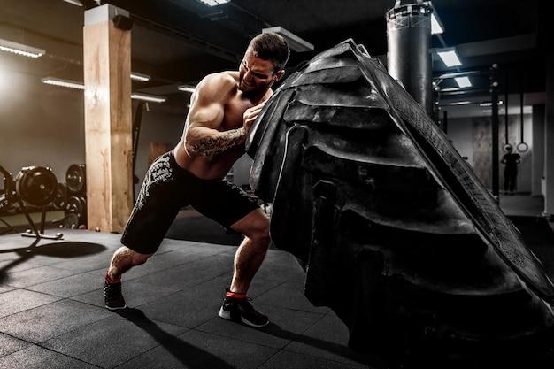 Hombre sin camisa volteando neumáticos pesados Foto Premium