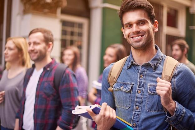 Hombre en el campus universitario con colegas Foto gratis