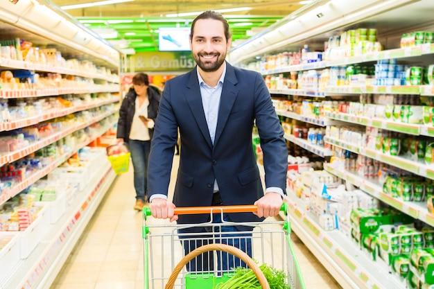 Hombre con carrito de compras en hipermercado Foto Premium