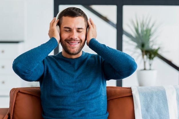 Hombre en casa en el sofá escuchando música Foto gratis