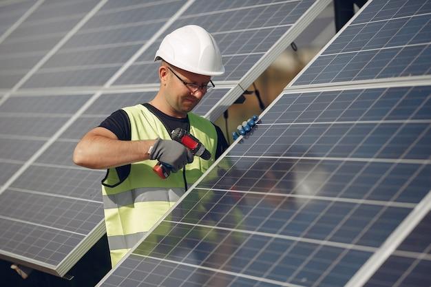 Hombre con casco blanco cerca de un panel solar Foto gratis