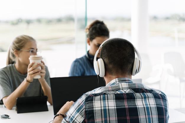 Hombre con cascos blancos sentados junto a dos chicas en la misma reunión de mesa Foto Premium
