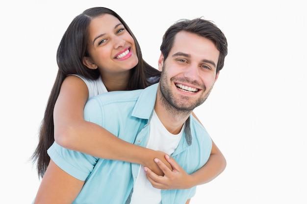 Hombre casual feliz dando piggy back girl bonita Foto Premium