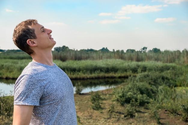 Hombre casual feliz respirando aire fresco en un campo con lago de fondo Foto Premium