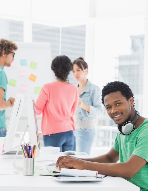 Hombre casual usando la computadora con colegas detrás en la oficina ...