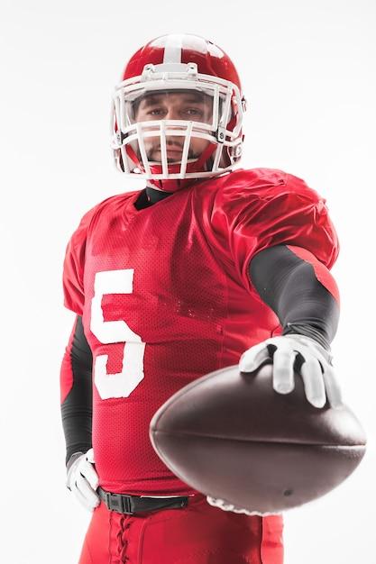 Hombre caucásico fitness como jugador de fútbol americano sosteniendo una pelota sobre fondo blanco. Foto gratis