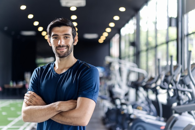 Hombre caucásico guapo con barba en ropa deportiva de color azul de pie y cruzando los brazos en el gimnasio o club de fitness. Foto Premium