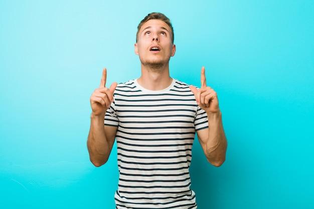 Hombre caucásico joven contra una pared azul que apunta al revés con la boca abierta. Foto Premium