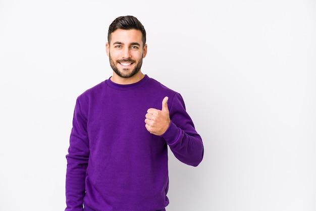 Hombre caucásico joven contra una pared blanca aislada sonriendo y levantando el pulgar hacia arriba Foto Premium